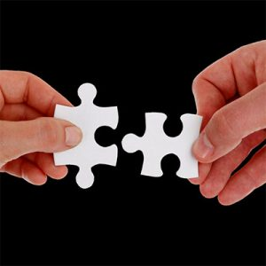 Hands putting two jigsaw pieces together