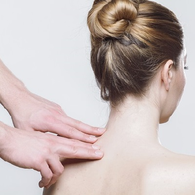Physiotherapist massaging a woman's shoulder