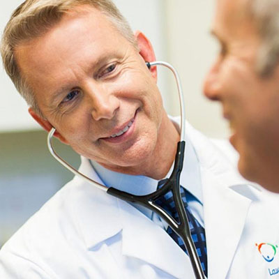 A doctor in a white coat using a stethoscope to listen to patients heart