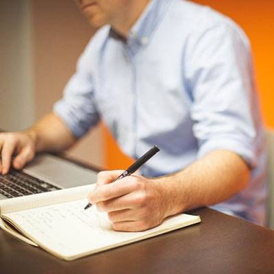 Man working on a laptop and writing in a notepad